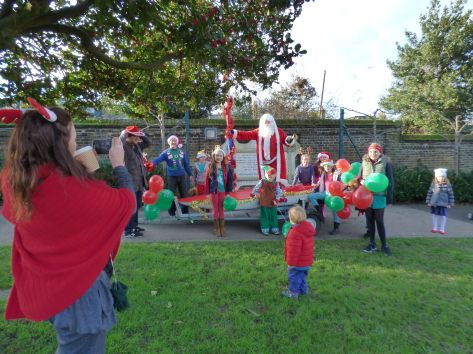 Father Christmas arrives safely  by boat at the Pleasaunce surrounded by his elves